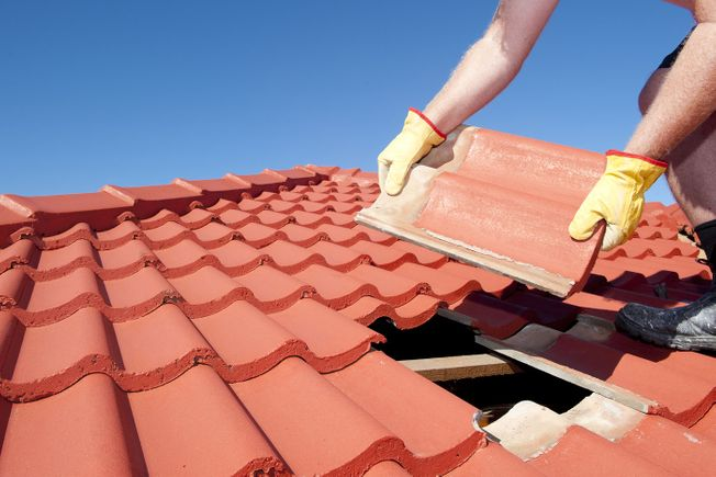 Roofer replacing a roof tile