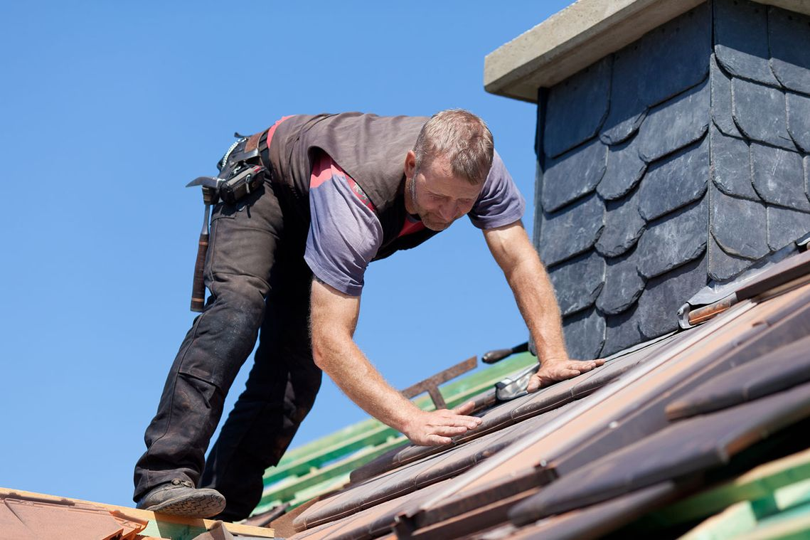 A roofer making repairs on a roof